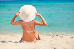 Una mujer se está sentando en una playa Fotografía de archivo