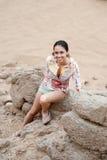 Una mujer se inclina en una roca en las montañas fotografía de archivo libre de regalías