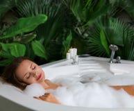 Una mujer se relaja en tina de baño caliente con espuma del jabón fotos de archivo