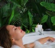 Una mujer se relaja en tina de baño caliente con espuma del jabón imagen de archivo