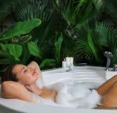 Una mujer se relaja en tina de baño caliente con espuma del jabón foto de archivo