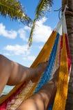 Una mujer se relaja en una hamaca en una playa del Caribe imágenes de archivo libres de regalías