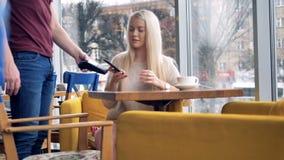 Una mujer se sienta cerca de una ventana del café y hace un pago de NFC almacen de video