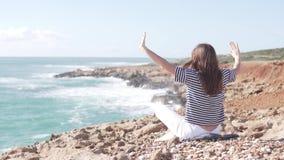 Una mujer se sienta con la suya de nuevo a la cámara y mirada en el mar almacen de video