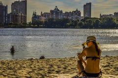 Una mujer se sienta en la playa fotos de archivo