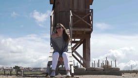 Una mujer se sienta en la torre y las miradas del rescate en el mar almacen de metraje de vídeo