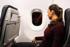Una mujer se sienta en la ventana de un aeroplano en la noche Foto de archivo