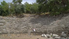 Una mujer se sienta en los pasos de piedra en la arena metrajes