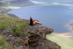 Una mujer se sienta en un acantilado sobre el lago imagenes de archivo