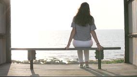 Una mujer se sienta en un banco por el mar y disfruta de la hermosa vista almacen de metraje de vídeo