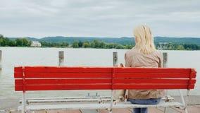 Una mujer se sienta en un banco rojo, admirando la vista del lago Visión posterior Resto en el lago Balatón en Hungría Foto de archivo