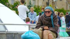 Una mujer sin hogar borracha se está sentando en la calle, encrespada para arriba almacen de video