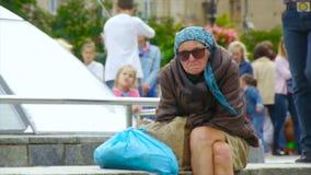 Una mujer sin hogar borracha se está sentando en la calle, encrespada para arriba metrajes
