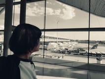 Una mujer sola en el aeropuerto mira el campo de aterrizaje fotos de archivo
