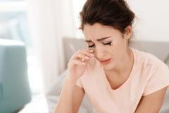 Una mujer sola está llorando solamente, su rimel ha fluido Ella se sienta en una cama en un cuarto brillante Imágenes de archivo libres de regalías
