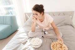 Una mujer sola está llorando solamente, su rimel ha fluido Ella se sienta en una cama en un cuarto brillante Fotografía de archivo libre de regalías
