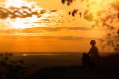 Una mujer sola se sienta en la roca y disfruta de la puesta del sol foto de archivo libre de regalías