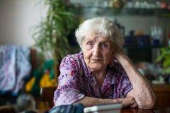 Una mujer solitaria mayor 85 años que se sientan en un cuarto en la tabla Imágenes de archivo libres de regalías