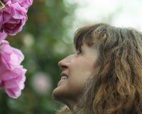 Una mujer sonríe para arriba en las rosas rosadas Imagen de archivo