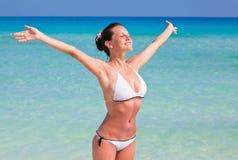 Una mujer sonriente está en la playa Fotografía de archivo