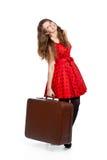 Una mujer sonriente está sosteniendo una maleta Fotos de archivo