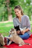 Una mujer sonriente hermosa con una cola de caballo y llevar una camisa rayada está abrazando con rato fornido dulce de tres perr imagen de archivo