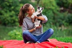 Una mujer sonriente hermosa con una cola de caballo y llevar una camisa rayada está abrazando con un perrito fornido dulce mientr foto de archivo libre de regalías