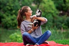 Una mujer sonriente hermosa con una cola de caballo y llevar una camisa rayada está abrazando con un perrito fornido dulce mientr imagen de archivo libre de regalías