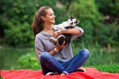 Una mujer sonriente hermosa con una cola de caballo y llevar una camisa rayada está abrazando con un perrito fornido dulce mientr fotografía de archivo libre de regalías