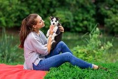Una mujer sonriente hermosa con una cola de caballo y llevar una camisa rayada está abrazando con un perrito fornido dulce mientr imagen de archivo