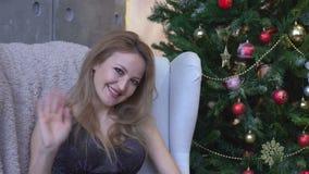 Una mujer sonriente hermosa en un vestido brillante que agita y que se sienta en una silla cerca de un árbol de navidad almacen de metraje de vídeo