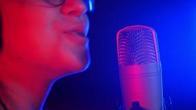 Una mujer sonriente joven en auriculares que canta en el estudio Iluminación de neón metrajes
