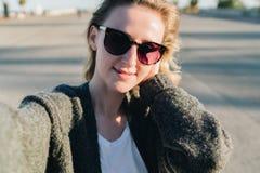 Una mujer sonriente joven se está colocando en un parque y está haciendo un selfie La muchacha en gafas de sol toma imágenes de s foto de archivo libre de regalías