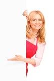 Una mujer sonriente que presenta detrás de un panell blanco Imagenes de archivo