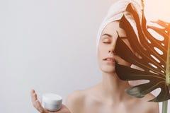 Una mujer sorprendida con una toalla en su cabeza sostiene una hoja y una crema verdes grandes para la cara foto de archivo libre de regalías