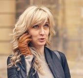 Una mujer sorprendida los jóvenes habla en el teléfono Imagenes de archivo