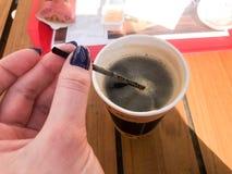 Una mujer sostiene con una manicura hermosa en sus fingeres un tubo en una taza de café natural fuerte caliente negro rápido de l fotos de archivo