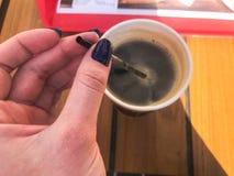 Una mujer sostiene con una manicura hermosa en sus fingeres un tubo en una taza de café natural fuerte caliente negro rápido de l foto de archivo libre de regalías