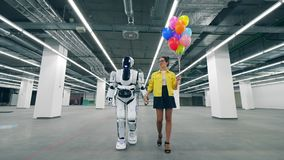 Una mujer sostiene los globos a disposición mientras que camina en un cuarto con el cyborg metrajes