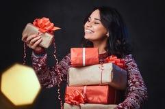 Una mujer sostiene los regalos de la Navidad Imagenes de archivo