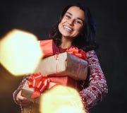 Una mujer sostiene los regalos de la Navidad Fotografía de archivo