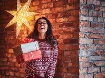 Una mujer sostiene los regalos de la Navidad foto de archivo libre de regalías