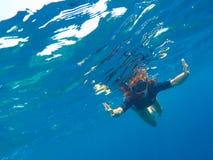 Una mujer subacuática en traje de baño negro y máscara, muchacha floja del pelo que bucea en máscara Fotos de archivo libres de regalías