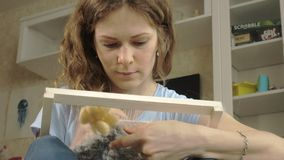 Una mujer teje en un telar que un bordado hermoso hizo del hilado, en un estudio casero, almacen de video