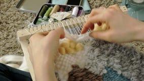 Una mujer teje en un telar que un bordado hermoso hizo del hilado, en un estudio casero, metrajes