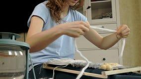 Una mujer teje en un telar que un bordado hermoso hizo del hilado, en un estudio casero, almacen de metraje de vídeo