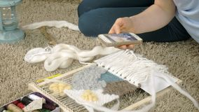 Una mujer teje en un telar que un bordado hermoso hizo del hilado, en un estudio casero, las fotografías en el teléfono metrajes