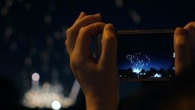 Una mujer tira los fuegos artificiales en un smartphone Celebración de los fuegos artificiales con el fondo de la luz de Bokeh almacen de metraje de vídeo