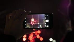 Una mujer tira los fuegos artificiales en un smartphone Fabricación del vídeo por el teléfono elegante de la exhibición hermosa d almacen de metraje de vídeo