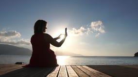 Una mujer toma imágenes en el smartphone, sentándose en el pontón en la cámara lenta almacen de video